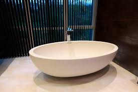 rustic bathroom interior with oval white standing stone tub and