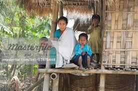 mishing tribal family on the verandah of their family home majuli