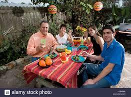 mexican american family enjoying a picnic in the backyard stock