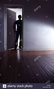 Dark Room Back View Of A Shadowy Male Walking Out Of A Dark Room Stock Photo