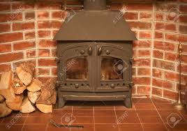 a wood burning stove in a red brick fireplace stock photo picture
