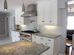 white kitchen design with grey quartz countertop and glass