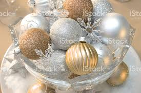 gold silver and white ornaments in a bowl stock