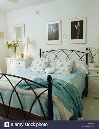 turquoise wool throw on wrought iron bed with turquoise striped