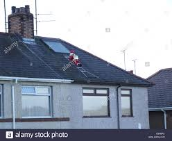 deliver presents christmas climbing house roof to deliver presents stock
