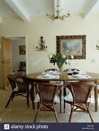 wicker chairs at oval antique table set for lunch in french
