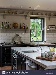 country kitchen with marble work tops aga and open shelving the