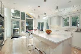 sleek modern white kitchen with eating area stock photo picture