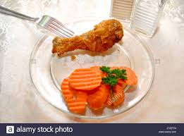 Small Chicken Carrots And Fried Chicken Leg On A Small Dinner Plate Stock Photo