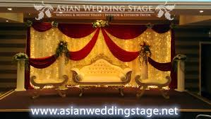 maroon and gold wedding gold sofa with maroon drapes and wedding stage