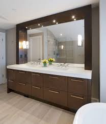 dark brown wooden bathroom vanity with white top and large mirror