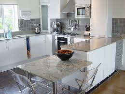 granite countertop white kitchen cabinets with dark backsplash