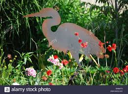 a metal garden sculpture of a great blue heron in a home flower