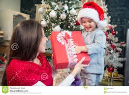 mother giving christmas present to her son stock photo image