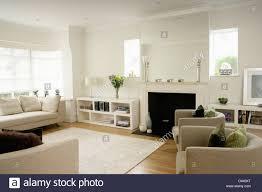 low white shelf unit beside fireplace in modern white living room