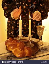 shabat candles woman lighting candles with a match and symbols of shabbat on