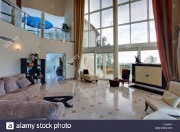 double height living room with view through glass wall of large