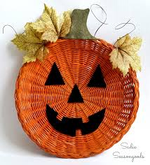 wicker paper plate holder repurposed as hanging jack o lantern