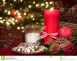 christmas cookies and milk waiting for santa claus in candle light