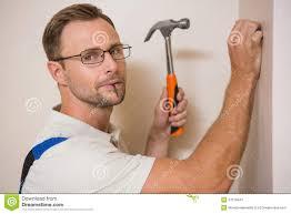 handyman hammering nail in wall while looking at camera stock