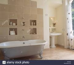 alcove shelving on beige tiled wall behind metallic clawfoot bath