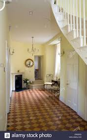 a large victorian style hallway with chequer board pattern floor