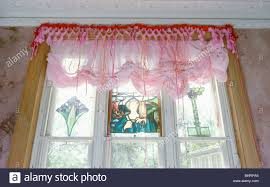 close up of pink voile festoon blind on stained glass window stock