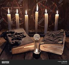 halloween background witch esoteric still life with black magic book and burning candles