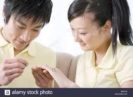 young man applying nail polish for woman u0027s fingernail stock photo