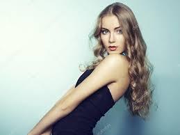 portrait of beautiful young blonde in black dress u2014 stock