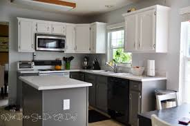 l shape light brown wooden kitchen cabinet with white counter top