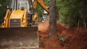 jcb bulldozer tractor digging soil with indian worker in