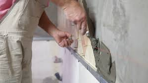 Installing Tile On Walls Man U0027s Hands Installing Ceramic Tile To A Kitchen Wall Close Up