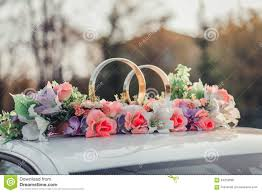 wedding car decoration with flowers and golden rings stock photo