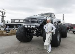 woman in white clothes standing next to grey ram monster truck