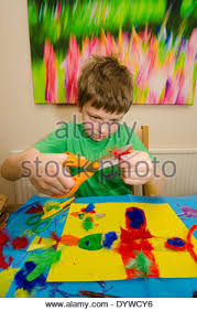 Art And Craft Room - eight year old boy doing arts and craft montage with glue scissors