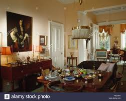 large oil painting above sideboard in traditional townhouse dining