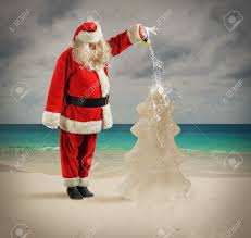 santa claus watering a christmas tree made of sand stock photo