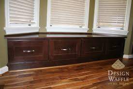 dark brown wooden window blind with 4 drawers connected by white