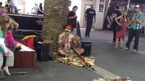 a funny aboriginal man performing with didgeridoo with awesome