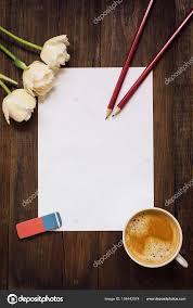 sur le bureau feuille blanche de papier de crayons de fleurs et de tasse de café