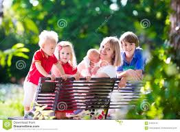 family with kids relaxing on a park bench stock photo image