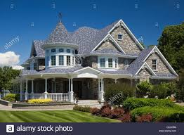 elegant grey stone white trim blue roof cottage style home in
