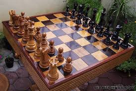 large wooden pieces chess pieces set on wooden folding board