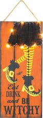 lighted wooden witch leg with yarn skirt hanging halloween sign