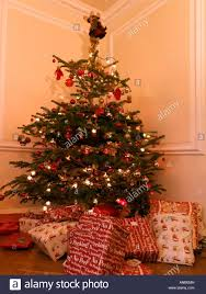 christmas tree with presents and angel on top in lounge stock