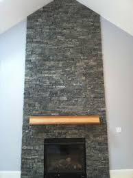 iron finished fireplace stone with brown wooden mantel shelf and