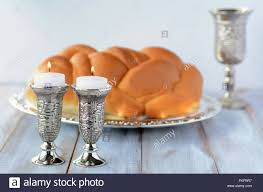 shabbat candles with challah bread and wine cup stock photo