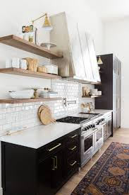 best 25 open shelving ideas on pinterest kitchen shelf interior kind of in love with the black cabinets modern kitchen with vintage rug subway tile backsplash open shelves and black cabinets with brass hardware