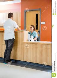 Free Reception Desk Patient Conversing With Nurse At Reception Desk Royalty Free Stock